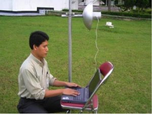 Gunadi with a Wokbolik connected to his computer. The Wokbolik is made out of a regular USB wireless adapter, a three-inch PVC pipe, and a regular cooking wok