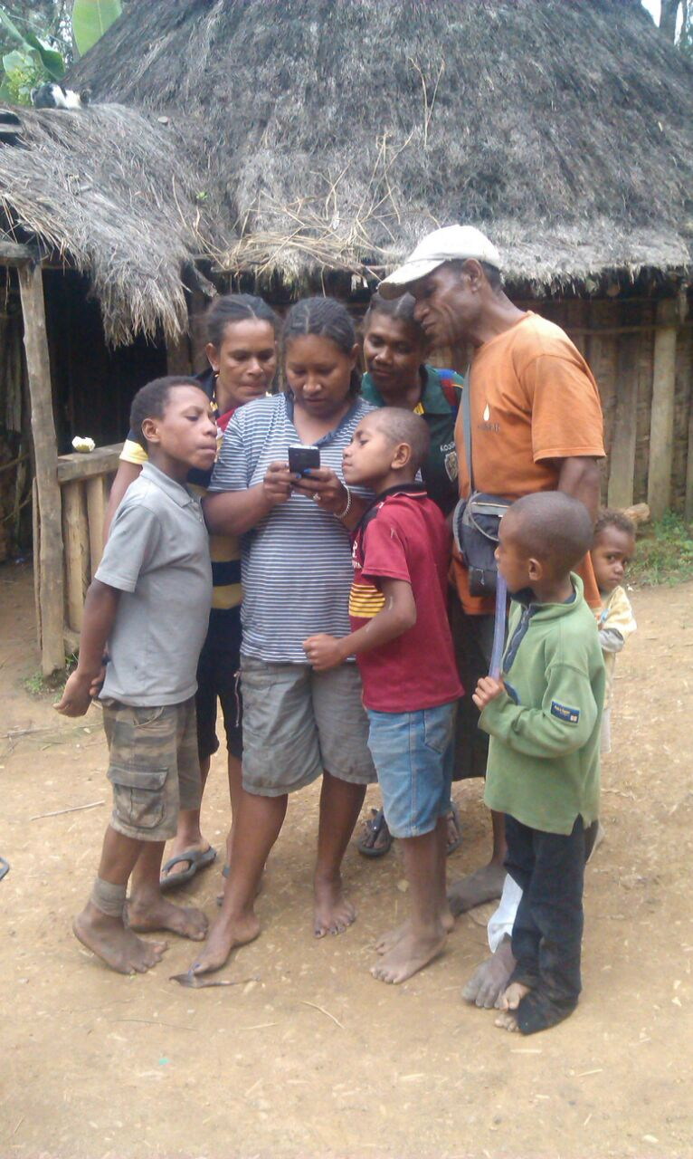 A family sharing a phone to read news on the Internet. Ba'eh Village, Aiyura Valley, Eastern Highlands Province, Papua New Guinea | Courtesy of Imae Iofa