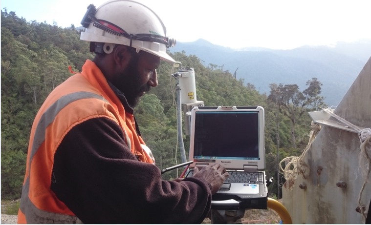 An Instrument Technician configures a laser transmitter at a remote mining site in PNG. Photo: Courtesy of Nathan Yehirai, Madang, Papua New Guinea