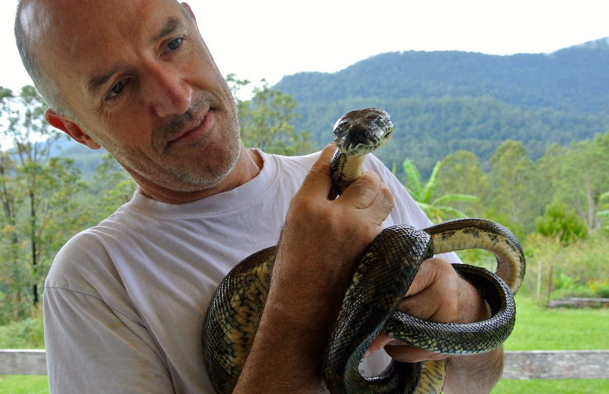 Paul Wilson with a carpet python, part of the range of fauna on his piece of bushland.