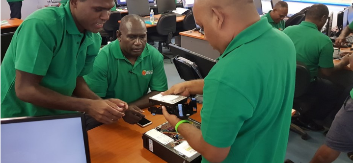 """Course participants during the computer disassembly exercises. Image: <a href=""""https://www.cybersafetypasifika.org/sites/default/files/CSP%20Newletter%202019%20Jan.pdf"""" target=""""_blank"""">Cyber Safety Pasifika</a>"""