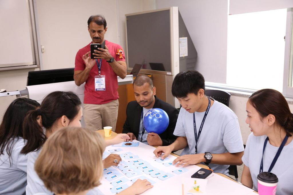 A photograph of APNIC's Sunni Chendi with a group of students playing IPGO at APIGA 2018.